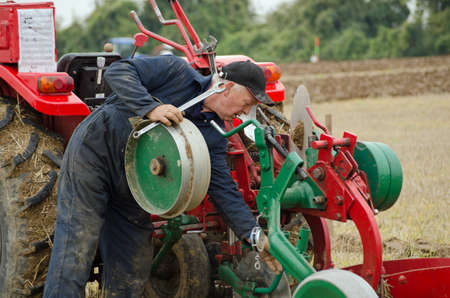 plough: BASINGSTOKE, UK  OCTOBER 12, 2014: Competitor David Chappell making adjustments to his plough while competing in the second day of the British National Ploughing Championships organised by the Society of Ploughmen.  Chappell won the Semidigger work, conve