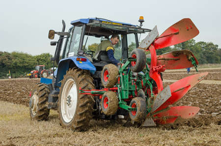 ploughing: BASINGSTOKE, UK  OCTOBER 12, 2014: A competitor in the one way ploughing  reversible class on the second day of the British National Ploughing Championships organised by the Society of Ploughmen. Accredited photographer