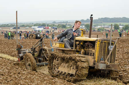 typically english: BASINGSTOKE, UK  OCTOBER 12, 2014: John Crowder competing in the second day of the British National Ploughing Championships organised by the Society of Ploughmen.  Taking part in the Crawler Tractor class on a Caterpillar tractor.  Accredited photographer