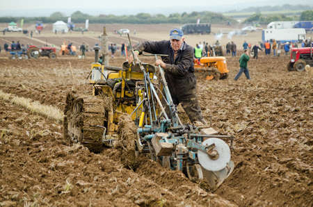 bri: BASINGSTOKE, UK  OCTOBER 12, 2014: Graham Soper making adjustments to his machinery while competing in the second day of the British National Ploughing Championships organised by the Society of Ploughmen.  Taking part in the Crawler Tractor class on a Bri