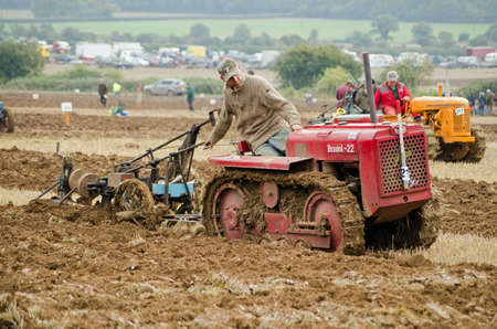 typically english: BASINGSTOKE, UK  OCTOBER 12, 2014: Chris Armstrong taking part  in the second day of the British National Ploughing Championships organised by the Society of Ploughmen.  Competing in the Crawler Tractor class on a Bristol tractor.  Accredited photographer Editorial