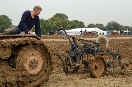 typically english: BASINGSTOKE, UK  OCTOBER 12, 2014: Graham Spark taking part in the second day of the British National Ploughing Championships organised by the Society of Ploughmen. Competing in the Crawler Tractor class on a Fordson E27N tractor Editorial