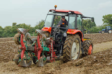 ploughing: BASINGSTOKE, UK  OCTOBER 12, 2014: A competitor carefully places his equipment while taking part  in the second day of the British National Ploughing Championships organised by the Society of Ploughmen Competing in the one way ploughing  reversible clas