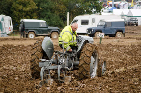 ploughing: BASINGSTOKE, UK  OCTOBER 12, 2014: A competitor on a vintage tractor taking part in the second day of the British National Ploughing Championships organised by the Society of Ploughmen Competing in the Ferguson ploughing championship on a vintage Fergu