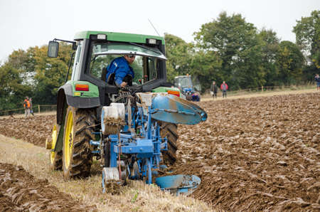 typically british: BASINGSTOKE, UK  OCTOBER 12, 2014: A competitor on a modern tractor taking part in the second day of the British National Ploughing Championships organised by the Society of Ploughmen Competing in the one way ploughing  reversible class.
