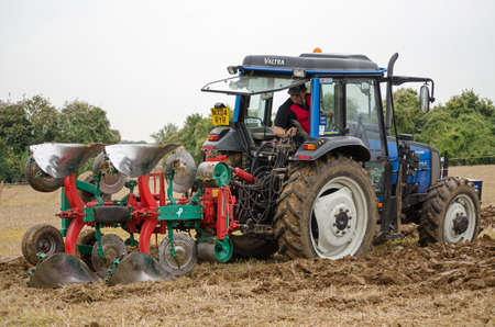 ploughing: BASINGSTOKE, UK  OCTOBER 12, 2014: Peter Alderslade competing on a Valtra tractor in the second day of the British National Ploughing Championships organised by the Society of Ploughmen.  Alderslade won the one way ploughing  reversible class.