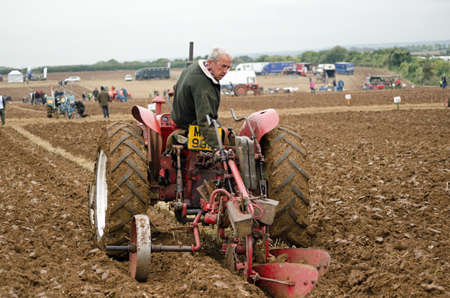 ploughing: BASINGSTOKE, UK  OCTOBER 12, 2014: A competitor adjusting his equipment during the second day of the British National Ploughing Championships organised by the Society of Ploughmen.  Competing in the National Vintage Ploughing Championship  Hydraulic Ploug Editorial