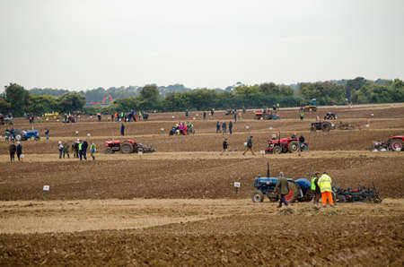 typically english: BASINGSTOKE, UK - OCTOBER 12, 2014:  A large field being used for the British National Ploughing Championships with competitors in various classes showing how straight they can plough furrows.