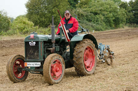 ploughing: BASINGSTOKE, UK - OCTOBER 12, 2014:  Farmer Tony Collister at the controls of a Fordson N vintage tractor during the British National Ploughing Championships, 2014.