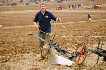BASINGSTOKE, UK - October 12, 2014:  Farmer John Fletcher demonstrates his expertise with a horse drawn plough during the British National Ploughing Championships.