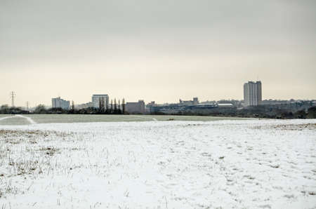 covered fields: View in early Spring across snow covered fields looking towards the skyline of the Hampshire market town Basingstoke.  Tall office blocks and apartments make up the familiar skyline.