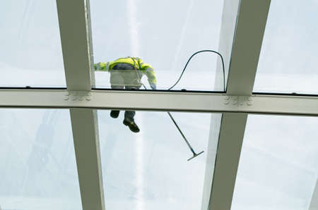 glass ceiling: View looking up towards a glass ceiling which is being washed by a specialist cleaner using a hose and special safety gear. Face obscured. Stock Photo