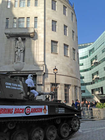 bbc: LONDON, UK - March 21, 2015:  The Stig on top of a tank outside BBC Broadcasting House delivering a petition in support of Top Gear presenter Jeremy Clarkson. Editorial