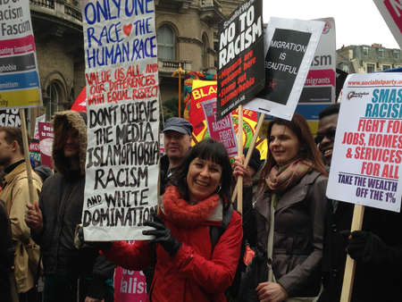 anti racist: LONDON, UK - MARCH 21, 2015:  A smiling woman holding a banner at a demonstration against racism and Islamaphobia in Westminster, Central London. Editorial