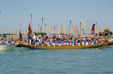 lido: VENICE ITALY  MAY 17 2015:  Rowers standing with their oars to attention during the Marriage with the Sea ceremony part of Festa della Sensa to mark Ascension Day in Venice Lido.
