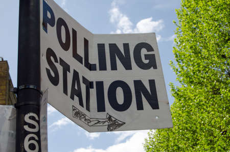 polling: A slightly wonky sign pointing towards a polling station for voters in the UK General Election. Stock Photo