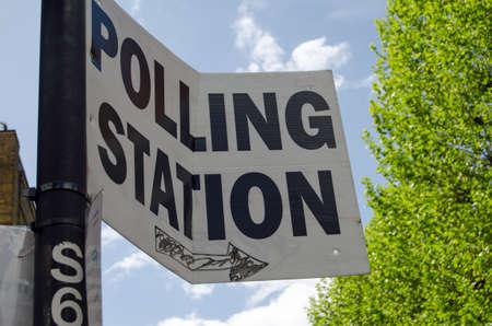 encuestando: Una señal ligeramente torcidas que apunta hacia un centro de votación para los votantes en las elecciones generales del Reino Unido.
