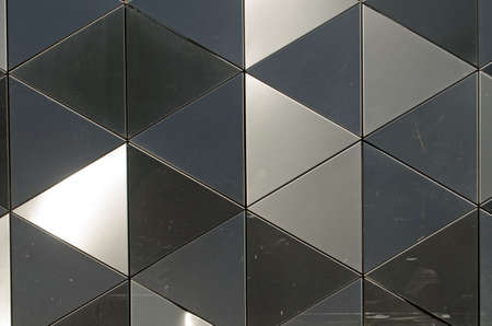 differing: Background with shiny metal triangles at differing angles reflecting the light.  Architectural detail. Stock Photo