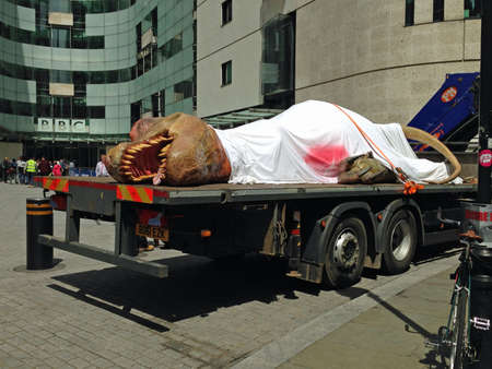 bloodied: LONDON UK  JUNE 1 2015:  The National Geographic Channel getting publicity for its TRex Autopsy programme by driving a life size model of a tyrannosaurus dinosaur around London.  Parked outside the BBC Broadcasting House headquarters in Portland Place Lon Editorial