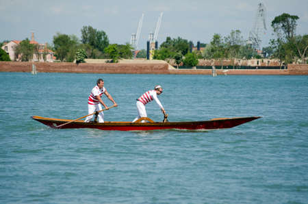 upright row: VENICE ITALY  MAY 17 2015:  Two oarsmen standing in the traditional style row their gondola across the Venetian Lagoon with the island of La Certosa in the background.