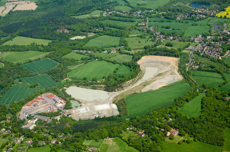 typically english: Aerial view of the lime quarry and brickworks at Betchworth in the Surrey Hills surrounded by the villages of Beare Green and South Holmwood in the Mole Valley close to Gatwick Airport.  View from above on a sunny Spring morning. Stock Photo