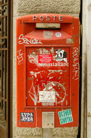 defaced: VENICE ITALY  MAY 24 2015:  An Italian post box covered in stickers and graffiti on a wall in Lido Venice.