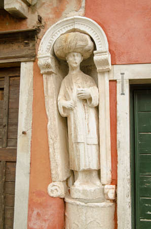 the merchant of venice: Historic statue of a man wearing a turban believed to be a member of the Mastelli Family who were Levantine merchants on display in Campo dei Mori in Venice Italy.