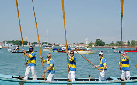 VENICE ITALY  MAY 17 2015:  Five Venetian men stand on their rowing boat holding their long oars straight up to attention during the historic Festa della Sensa ceremony where the city marries the sea.  Many boats a oarsmen take part in the celebration whi