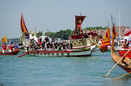 important people: VENICE ITALY  MAY 17 2015:  A boat full of very important people musicians and oarsmen arrives at the historic Festa della Sensa ceremony in Venice where the city marries the sea.  The Patriarch of Venice is on board the boat rowed by an allwoman team.
