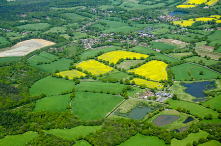 typically english: View from above of fields of yellow oil seed rape growing around the Surrey villages of Capel and Newdigate in May in rural England.