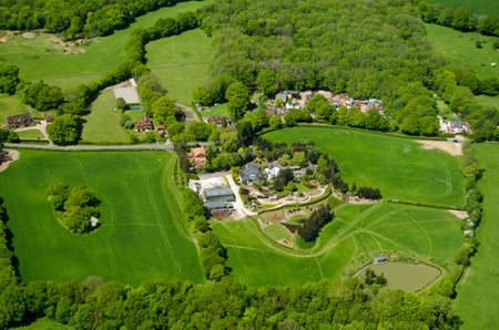 View from an airplane of expensive homes and farmland at Russ Hill in Surrey close to Gatwick Airport in countryside.