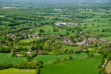 typically english: View from an airplane of the village of Charlwood inthe Surrey Hills.  A game of cricket is being played in the May sunshine on the village pitch.