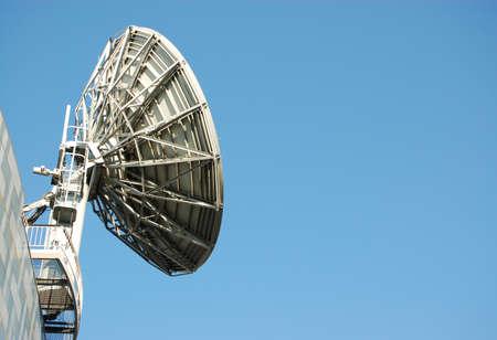 cielo azul: Un plato grande, industrial sat�lite utilizado en el Industy comunicaciones contra un cielo azul en un d�a soleado de verano con espacio para la copia. Foto de archivo