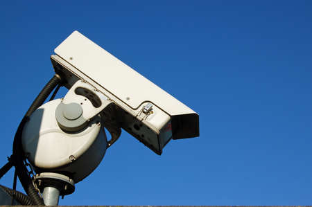 closed circuit: A closed circuit security camera photographed against a clear blue sky with space for copy.