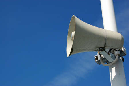 public address: A public address system speaker against a blue sky on a sunny day with space for copy Stock Photo