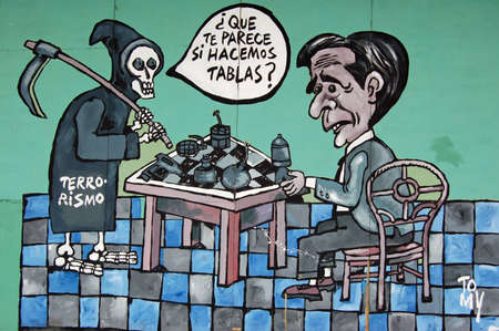 hoarding: HAVANA, CUBA - November 19, 2005: Political mural painted on a hoarding overlooking the pavement in the Vedado district of Havana showing Death by terrorism playing a board game with President George W Bush using weapons as counters.  A low point in relat