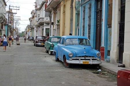 residential street: HAVANA, CUBA - NOVEMBER 19, 2005: Pedestrians and parked classic cars in a residential street in Havanas Vedado district.  Fuel is in short supply so most people walk through the city.