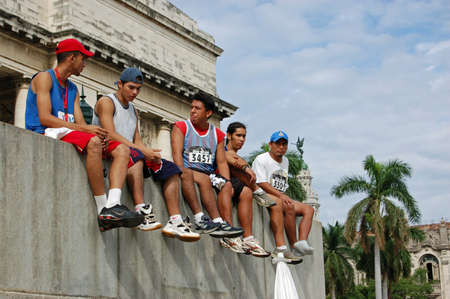 recuperating: HAVANA, CUBA - NOVEMBER 20, 2005: Competitors in the annual Havana marathon resting on the steps of the Capitolio building after the race.