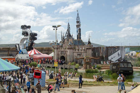 WESTON-SUPER-MARE, UK - AUGUST 26, 2015:  View from above of crowds of visitors enjoying Dismaland at the traditional Somerset seaside resort of Weston-Super-Mare.  Attractions include a dilapidated Cinderella Castle and a fountain and waterslide made fro