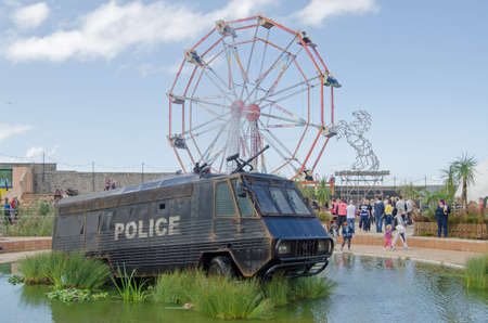 WESTON-SUPER-MARE, UK - AUGUST 26, 2015:  A former crowd control police van with water cannon from Northern Ireland now converted to a fountain, there's a water slide at the other side.  Part of the parody seaside attractions at the traditional seaside re Editorial