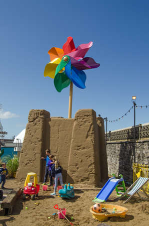children sandcastle: WESTON-SUPER-MARE, UK - AUGUST 26, 2015:  Children playing beside a giant sandcastle topped with a colourful windmill at the traditional seaside resort of Weston-Super-Mare, Somerset.