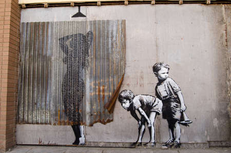iron curtains: WESTON-SUPER-MARE, UK - AUGUST 26, 2015:  Banksy graffiti style picture of young boys peeping at a woman taking a shower.  Painted on the wall of the disused Tropicana swimming pool at the traditional seaside resort of Weston-Super-Mare in Somerset.  On p