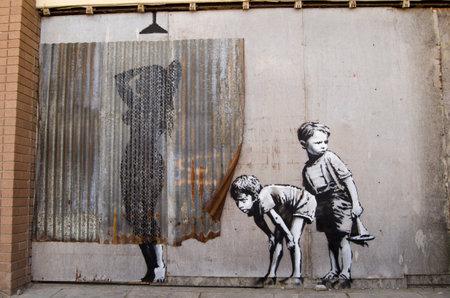 Weston-super-Mare, Verenigd Koninkrijk - 26 augustus 2015: Banksy Graffiti stijl beeld van de jonge jongens gluren bij een vrouw die een douche. Geschilderd op de muur van de in onbruik geraakte Tropicana zwembad aan de traditionele badplaats Weston-Super-Mare in Somerset. Op p