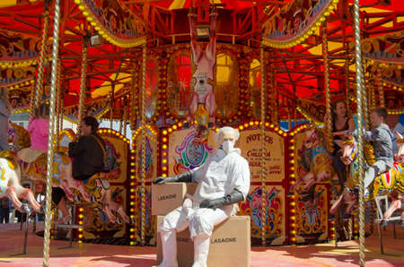parody: WESTON-SUPER-MARE, UK - AUGUST 26, 2015:  An abattoir worker resting on a box of carousel horsemeat lasagne at the steam gallopers ride, Dismaland.  The Banksy inspired parody of a theme park has attracted thousands of visitors to Weston-Super-Mare, Somer