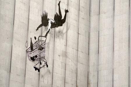 LONDON, Großbritannien - 15. Juni 2015: Banksy Graffiti an der Seite eines ausgedienten Bürohaus in einem teuren Teil der Londoner Innenstadt, die eine Frau Shopper fallen mit ihren Einkaufswagen und Waren, einschließlich einer Flasche Champagner und Perlenkette. Auf öffentlichen displ Standard-Bild - 44457221
