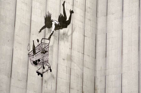 LONDON, UK - JUNE 15, 2015:  Banksy graffiti on the side of a disused office block in an expensive part of Central London showing a woman shopper falling with her shopping trolley and goods including a champagne bottle and pearl necklace.  On public displ