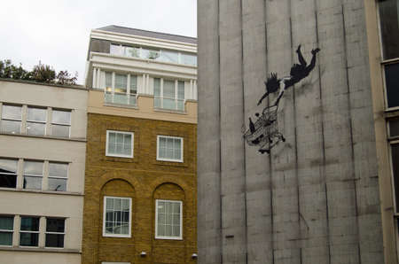 Banksy graffiti on a disused London office block showing a wealthy woman shopper falling with her trolley of luxury goods. On public display in Mayfair, viewed from pavement. Editorial