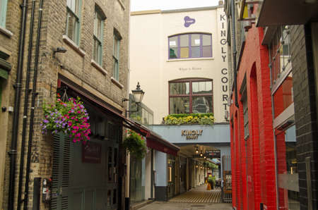 kingly: LONDON, UK - JULY 16, 2015: Alley entrance to Kingly Court near Carnaby Street in Soho, London.  The courtyard is home to fashionable restaurants, shops and a yoga studio.