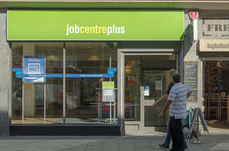 WESTON-SUPER-MARE, UK - AUGUST 26, 2015:  Two men walking past the Job Centre Plus government employment office in the centre of Weston-Super-Mare, Somerset on a sunny day in August. Editorial