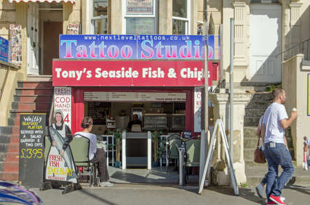 typically british: WESTON-SUPER-MARE, UK - AUGUST 26, 2015: A tattoo parlour above a fish and chip shop on the seafront at the traditional British resort of Weston-Super-Mare, Somerset.  The resort has been in decline for several years. Editorial